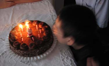 Jon blowing out candles on a chocolate cake