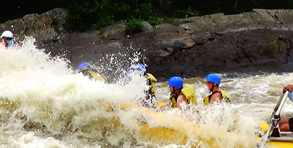 Raft nearly covered by whitewater